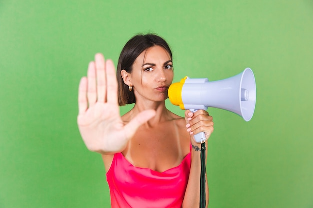 Mulher estilosa em vestido de seda rosa sobre verde, com megafone, isolado, mostrar gesto de parada com cara séria