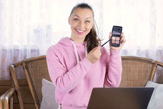 Mulher estilosa testando novos produtos cosméticos e processo de gravação na câmera de vídeo