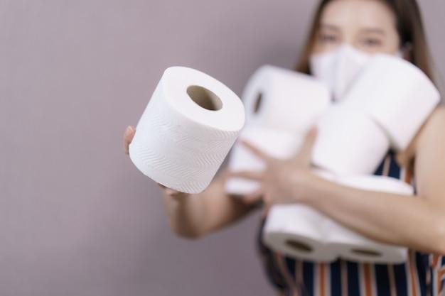Mulher estocando papel higiênico para quarentena em casa, mantém muitos rolos de papel higiênico na mão.