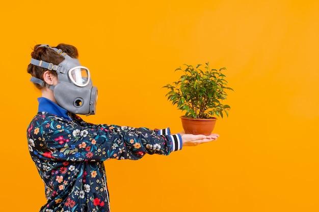 Mulher estranha elegante no respirador posando com uma flor no vaso sobre fundo laranja