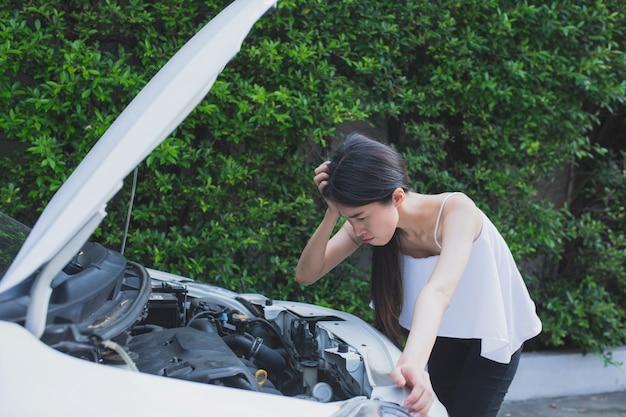 Mulher estressada asiática perto de carro quebrado, sentindo-se desesperada