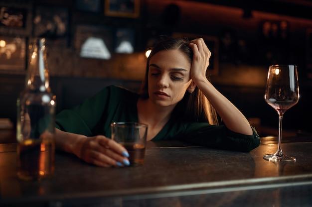 Mulher estressada bebe bebida alcoólica no balcão do bar. uma pessoa feminina em um bar, emoções humanas, atividades de lazer, vida noturna