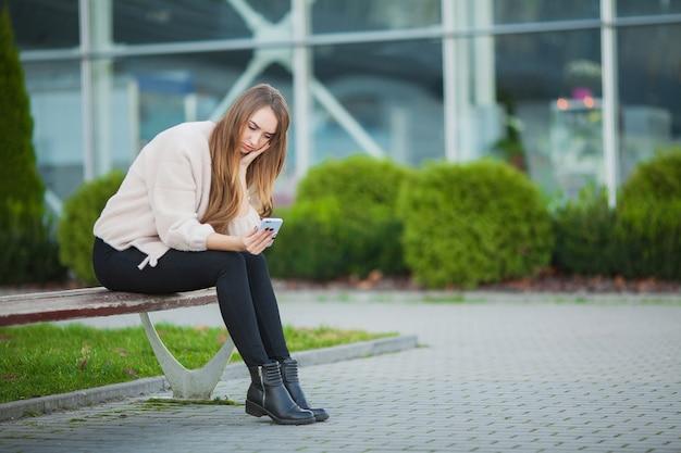 Mulher estressada do trabalho enquanto está sentado ao ar livre, imprensa de colegas