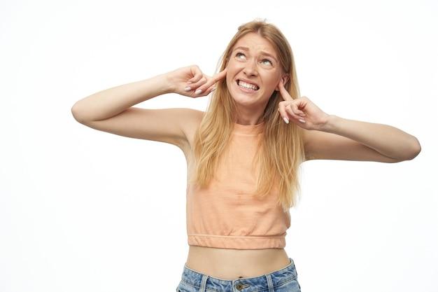 Mulher estressada e infeliz, com longos cabelos loiros, fecha as orelhas com os dedos, olhando para cima