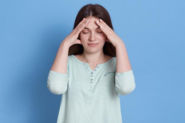 Mulher estressada e irritada mantendo os dedos na testa
