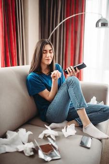 Mulher estressada em emoção sentada no sofá comendo doces, conceito de depressão feminina