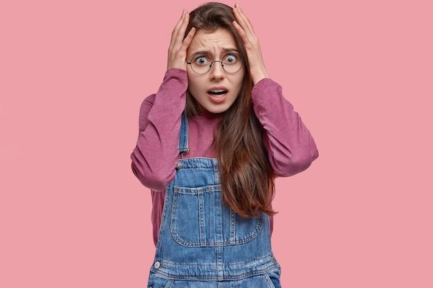 Mulher estressada fica com as mãos na cabeça em pânico, tem alguns problemas, olha com expressão assustada, vestida com roupas da moda