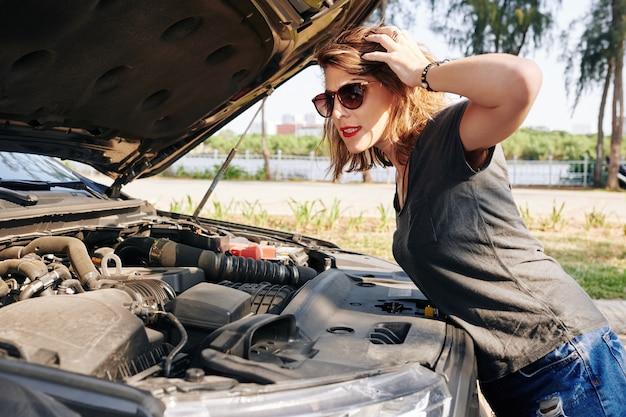 Mulher estressada olhando para o motor de um carro quebrado