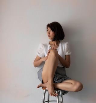 Mulher estressada sentada contra a parede, com sentimento triste e experimentado, emoção negativa