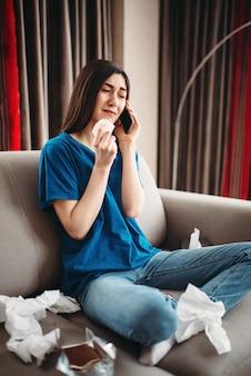 Mulher estressada sentada no sofá comendo chocolate, conceito feminino de depressão