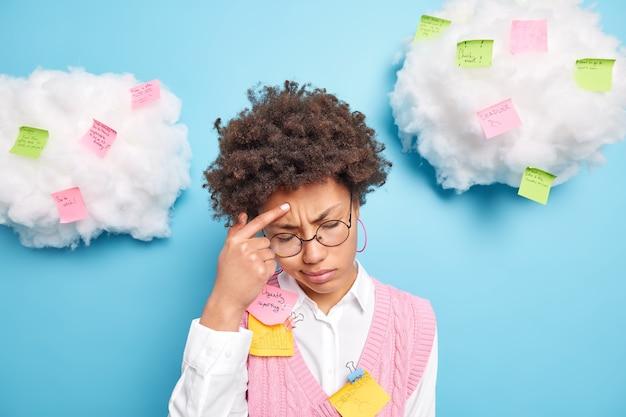 Mulher estressada tem muitas coisas a fazer tenta se concentrar tem dor de cabeça usa óculos redondos, camisa branca e colete isolado sobre a parede azul com nuvens brancas acima