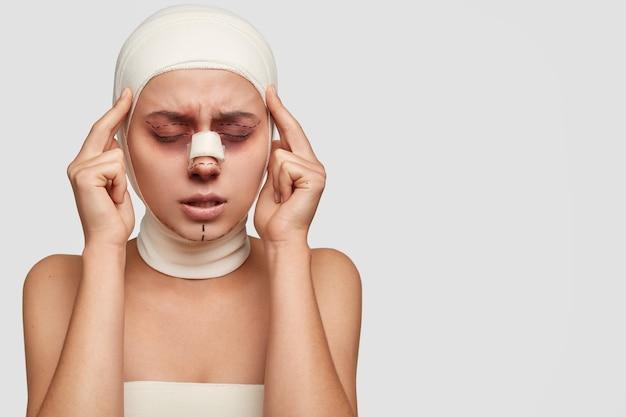Mulher estressante e doente mantém os dedos indicadores nas têmporas, fecha os olhos, sente dor após uma operação cirúrgica malsucedida