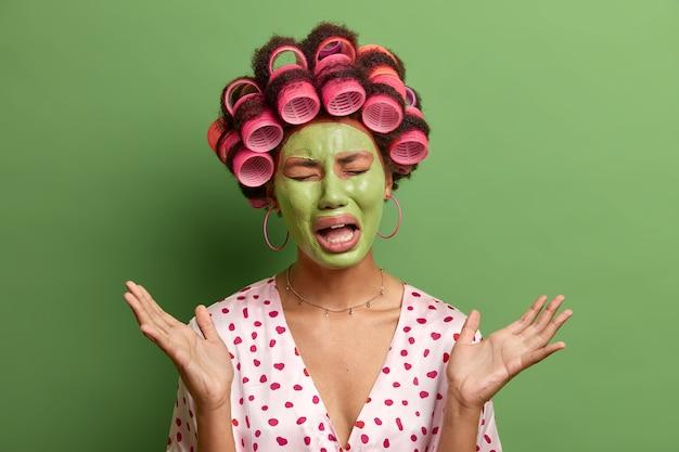 Mulher estressante e frustrada chora em desespero, levanta a mão, descobre notícias trágicas, aplica máscara facial verde nutritiva, rolos de cabelo, fim de semana estragado, posa em casa contra o verde