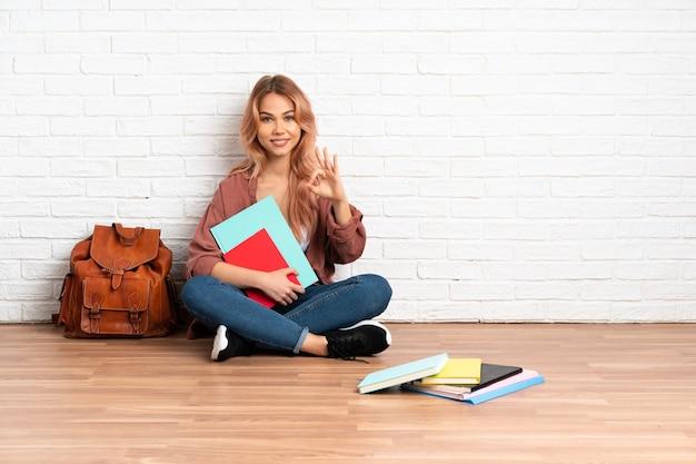 Mulher estudante adolescente de cabelo rosa sentada no chão dentro de casa mostrando sinal de ok com as duas mãos