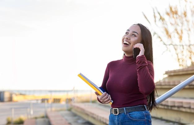 Mulher estudante asiática feliz e sorridente enquanto fala ao telefone