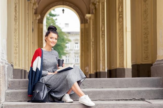 Mulher estudante está lendo o livro nas escadas da universidade.