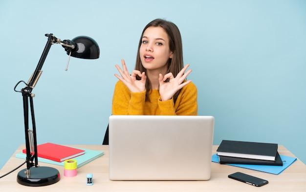 Mulher estudante estudando em sua casa isolada na parede azul, mostrando um sinal de ok com os dedos