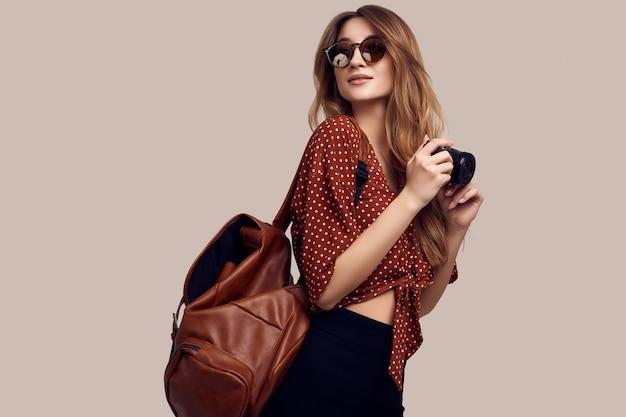 Mulher estudante sorridente com mochila e câmera saindo de férias