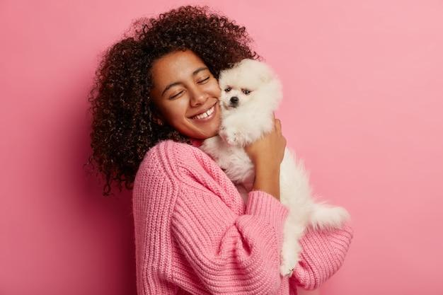 Mulher étnica abraça cachorro branco com prazer e amor, sorri gentilmente, gosta de estar junto com seu animal de estimação favorito, tem relacionamento amigável, prepara-se para exposição de cães.