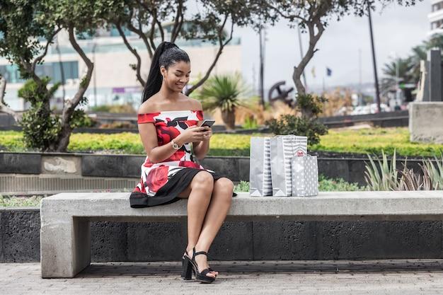 Mulher étnica adulta usando smartphone enquanto está sentado no banco ao lado de sacos de papel no centro da cidade