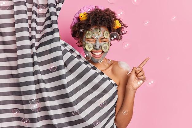 Mulher étnica alegre aplica máscara de beleza no rosto indica poses de lado no banheiro, indo tomar banho, risos, positivamente, tem corpo limpo, pele saudável preparada.