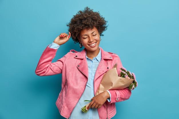 Mulher étnica alegre e despreocupada dançando alegremente, segurando um buquê de flores embrulhado em papel