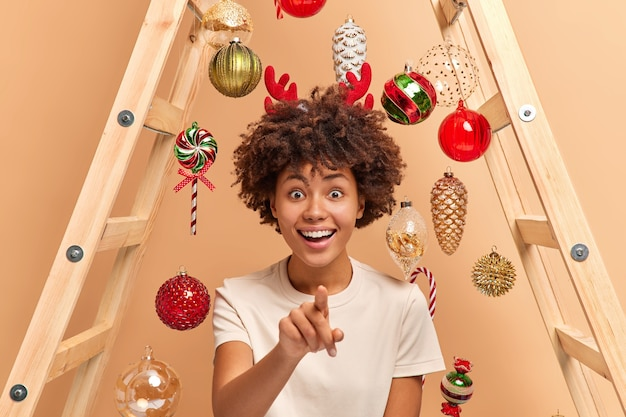 Mulher étnica atraente alegre com cabelo encaracolado indica diretamente para a câmera tem um largo sorriso se prepara para a celebração do feriado usa escada para pendurar brinquedos de natal vê algo incrível na frente