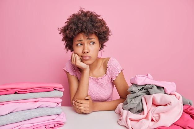 Mulher étnica cansada e desapontada triste desvia o olhar, pensativa, perdida em pensamentos, enquanto dobra a roupa suja em casa se senta à mesa isolada sobre o rosa