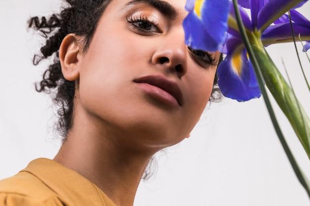 Mulher étnica com buquê de flores azuis