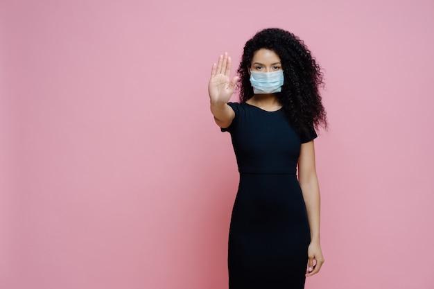 Mulher étnica com cabelo encaracolado faz gesto de parada com a palma da mão, diz não ao coronavírus
