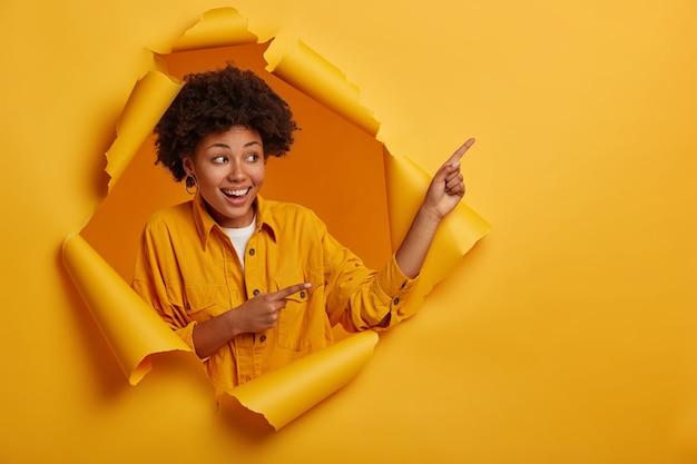 Mulher étnica de aparência amigável recomenda espaço em branco para seu conteúdo de publicidade, fica satisfeita em uma parede de buraco de papel, sorri feliz