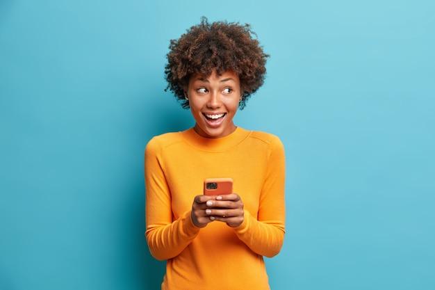Mulher étnica de cabelo encaracolado positiva usa telefone celular, verifica mensagens e lê notícias, segura o celular moderno em mãos, com uma expressão curiosa e feliz à direita isolada sobre a parede azul