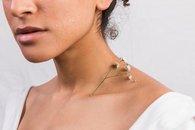 Mulher étnica de colheita com planta no pescoço