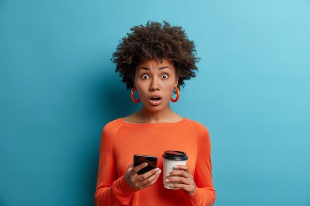 Mulher étnica emocionada e estupefata lê notícias impressionantes na internet, segura o celular na mão, recebeu um código promocional para uma boa venda, bebe café para viagem, usa suéter laranja, posa contra a parede azul