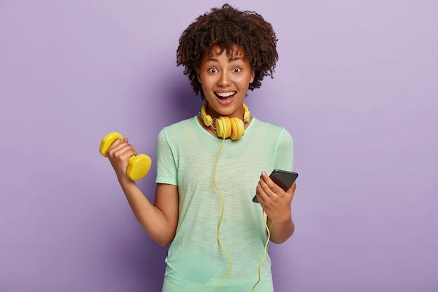 Mulher étnica encantada conversa no celular, ouve música durante os exercícios de jogigng, se aquece, segura halteres