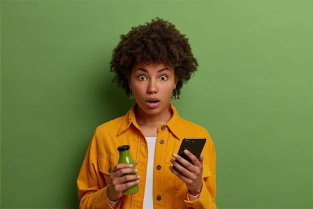 Mulher étnica encaracolada e emocional atordoada encara com os olhos cheios de choque, lê notícias surpreendentes on-line no site, segura um telefone celular moderno, copo de suco de vegetais verdes, mantém uma dieta saudável