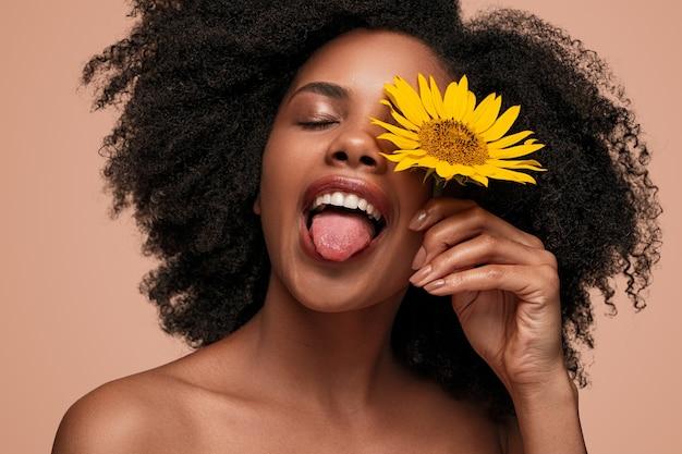 Mulher étnica engraçada com flor amarela