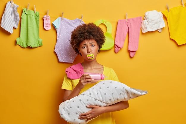 Mulher étnica exausta, mãe cuida do bebê, tem expressão cansada depois de lavar a roupa, alimenta o bebê com leite da mamadeira, não suporta choro de criança, posa em casa contra a parede amarela