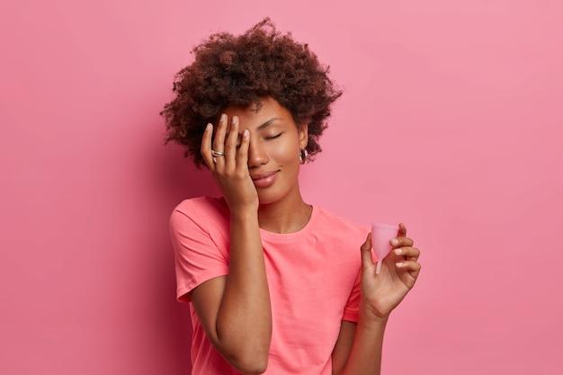 Mulher étnica experiente melhora sua menstruação usando copo menstrual lavável de látex ecologicamente correto zero desperdício, faz o rosto com a palma da mão e fecha os olhos, gosta de novo suprimento para higiene pessoal, bom absorvente