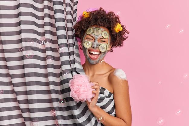 Mulher étnica exultante se diverte na ducha toma banho segura pose de esponja nua atrás da cortina passa por tratamentos de beleza aplica máscara de argila nutritiva