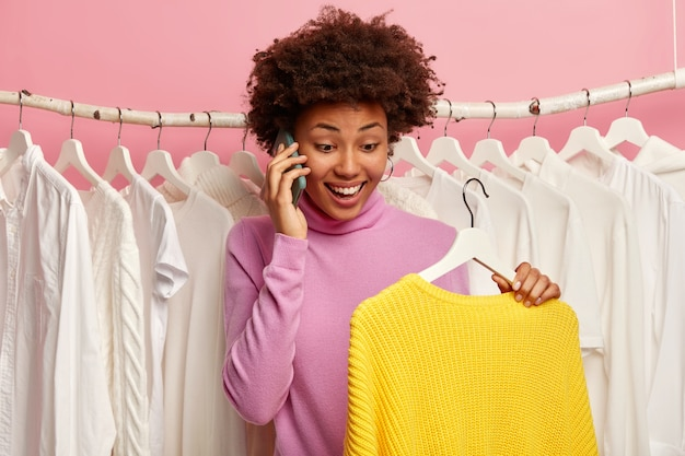 Mulher étnica feliz conversa ao telefone com um amigo, pede conselhos sobre o que melhor vestir para namorar