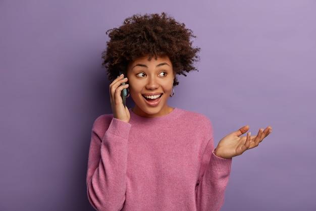 Mulher étnica feliz fala ao telefone, desvia o olhar e gesticula, comenta com impressão sua ida ao teatro, vestida com macacão casual, concentrada à parte, com sorriso dentuço isolado na parede roxa
