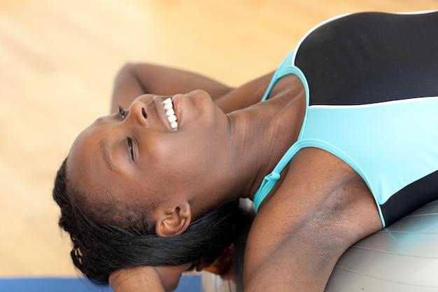 Mulher étnica feliz trabalhando com uma bola de pilates