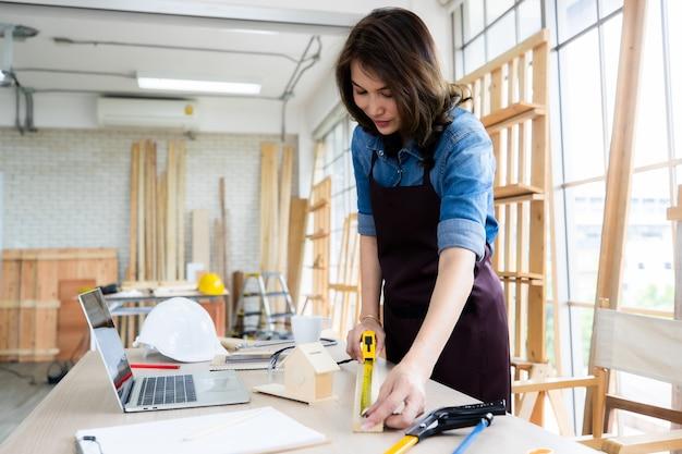 Mulher étnica positiva no avental sorrindo e medindo a tábua de madeira na mesa perto do laptop enquanto trabalhava em carpintaria leve