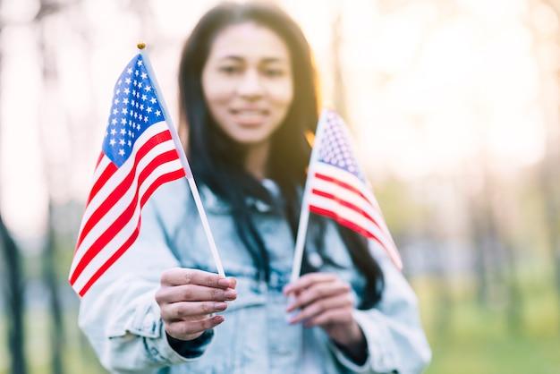 Mulher étnica, segurando, lembrança, bandeiras americanas