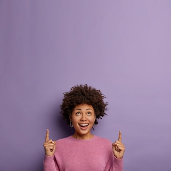 Mulher étnica sorridente e alegre aponta acima, anuncia um objeto legal