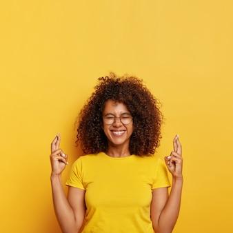 Mulher étnica supersticiosa alegre espera pelo melhor, cruza o dedo para dar sorte, ansiosa para conseguir uma posição em uma grande empresa, sorri com alegria, usa óculos e camiseta, isolada na parede amarela.