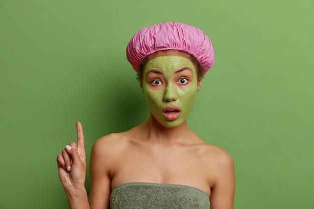 Mulher étnica surpresa, pontos acima, e expressão questionada aplica máscara facial verde argila para rejuvenescer pontos da pele surpreendentemente acima isolados sobre parede verde