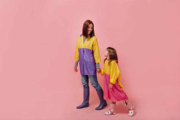 Mulher eu com menina criança bonita em capas de chuva. mãe filha pequena isolada