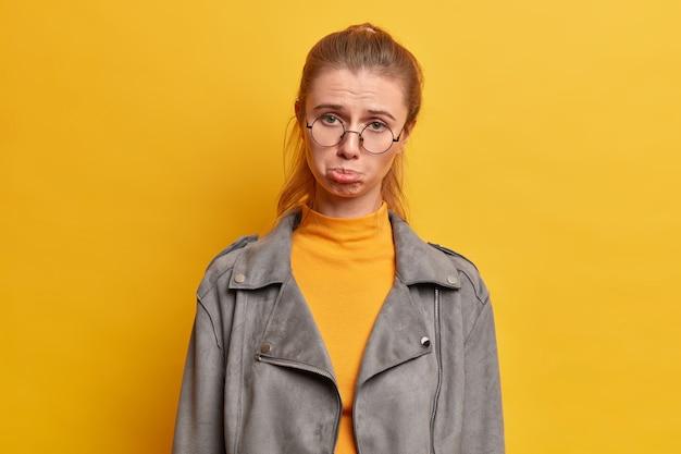 Mulher europeia adulta, triste e miserável faz expressão de pena, deprimida por angústia, tem maus sentimentos, usa óculos redondos e jaqueta cinza